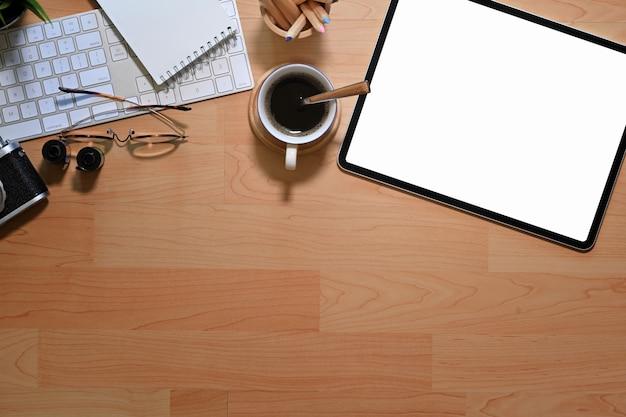 Hölzerner schreibtisch des arbeitsplatzbüros mit tablette, kamera, filmen und büroartikel des leeren bildschirms Premium Fotos