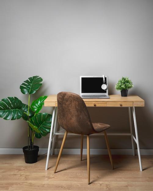 Hölzerner schreibtisch mit stuhl und grauem laptop Kostenlose Fotos