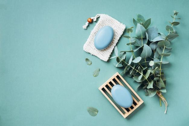 Hölzerner seifenteller, seife, eukalyptus über grünem hintergrund. null abfall, natürliche organische badezimmerwerkzeuge. Premium Fotos