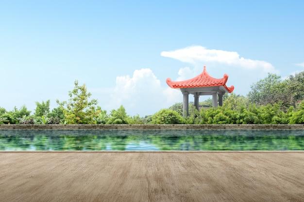 Hölzerner weg mit chinesischem gazebogebäude mit teich und bäumen Premium Fotos