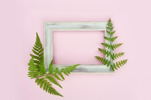 Hölzerner weißer fotorahmen und grünblätter auf leichtem rosa Premium Fotos