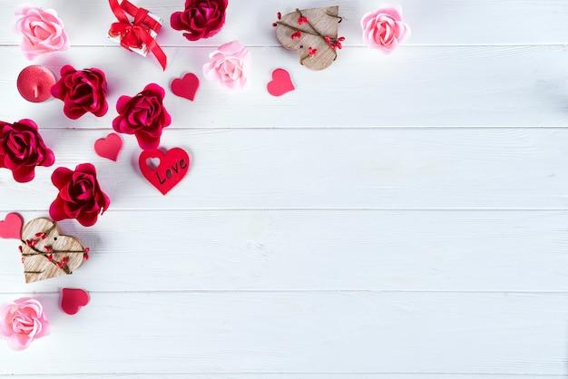 Hölzerner weißer hintergrund mit roten herzen und blumen. valentinstag Premium Fotos