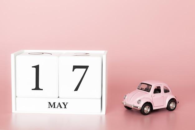 Hölzerner würfel der nahaufnahme am 17. mai. tag 17 des mai-monats, kalender auf einem rosa hintergrund mit retro- auto. Premium Fotos