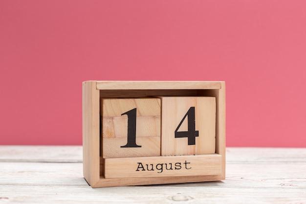Hölzerner würfelformkalender für den 14. august auf hölzerner tischplatte Premium Fotos