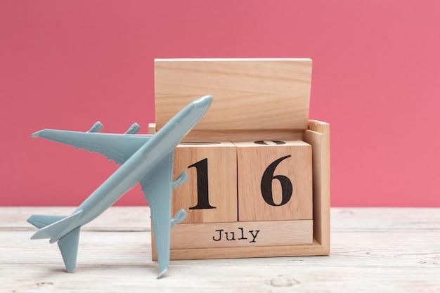 Hölzerner würfelformkalender für den 16. juli auf hölzerner tischplatte Premium Fotos