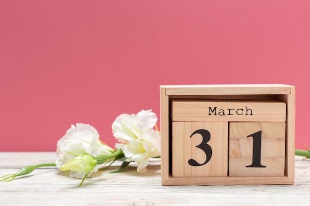 Hölzerner würfelformkalender für den 31. märz auf hölzerner tischplatte Premium Fotos