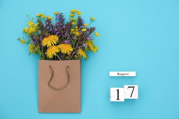 Hölzerner würfelkalender am 17. august und bunte rustikale blumen des feldes im handwerkspaket Premium Fotos