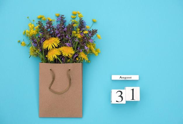 Hölzerner würfelkalender am 31. august und bunte rustikale blumen des feldes Premium Fotos