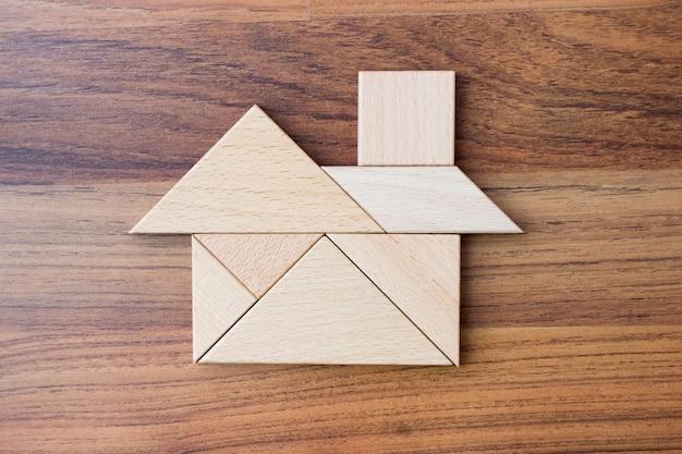 Hölzernes dreieckpuzzlespiel oder -puzzle in der hauptform. traumhaus-konzept. Premium Fotos