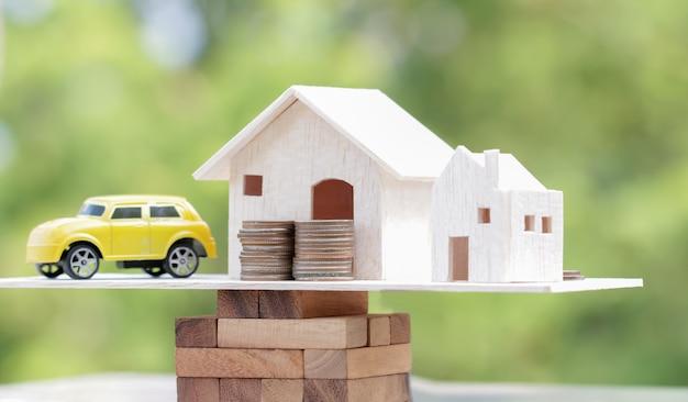 Hölzernes haus, auto mit stapel geldmünzen auf holzklotzskala Premium Fotos