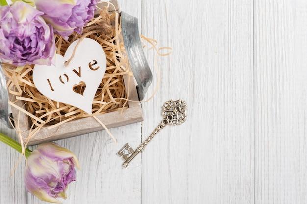 Hölzernes herz in der weinlesegeschenkbox mit schlüssel und purpurroten tulpen Premium Fotos