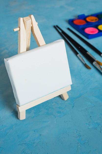 Hölzernes kleines weißes leeres gestell mit malerpinsel auf blauem strukturiertem hintergrund Kostenlose Fotos