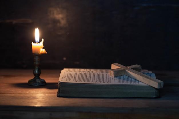 Hölzernes kreuz, das auf eine geöffnete bibel legt Kostenlose Fotos
