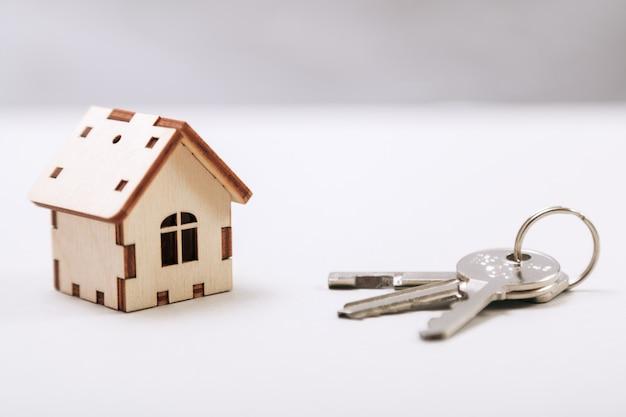 Hölzernes miniaturhaus mit türschlüsseln schließen oben. immobilien-konzept. kleines spielzeugholzhaus mit schlüsseln mit kopienraum Premium Fotos