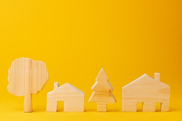 Hölzernes minihausmodell auf gelbem hintergrund Premium Fotos