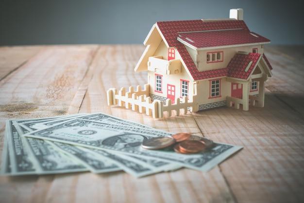 Hölzernes musterhaus mit geld auf hölzerner tabelle mit dem kopienraum bereit Premium Fotos