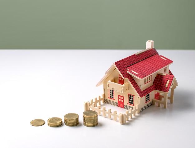 Hölzernes musterhaus mit geld auf weißer tabelle mit dem kopienraum bereit Premium Fotos