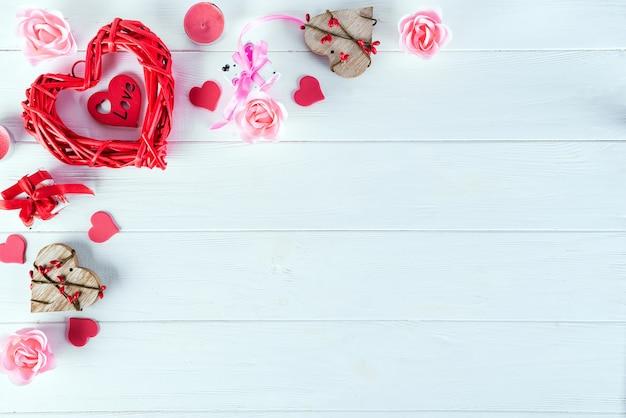 Hölzernes rotes herz auf weißem hölzernem hintergrund. valentinstag hintergrund Premium Fotos
