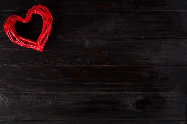 Hölzernes rotes herz, das am dunklen hölzernen hintergrund hängt. valentinstag hintergrund Premium Fotos