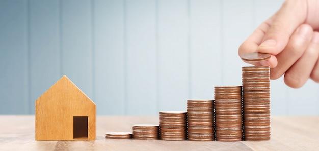 Hölzernes spielzeughaus hypothekeneigentum-ausgangskonzept, das in der hand für familie, münzen kauft Premium Fotos