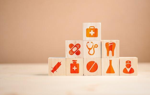 Hölzernes würfelstapeln der gesundheitswesenmedizin- und -krankenhausikone auf tabelle. Premium Fotos