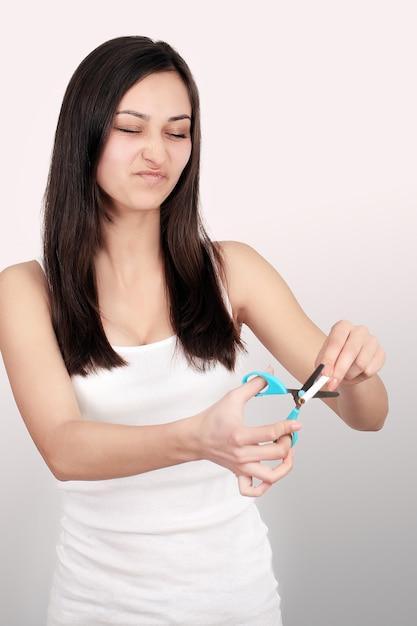 Hör auf zu rauchen konzept. junge frau schnitt zigaretten mit dem glücklichen lächeln der schere. konzentrieren sie sich auf hand, schere und zigaretten Premium Fotos