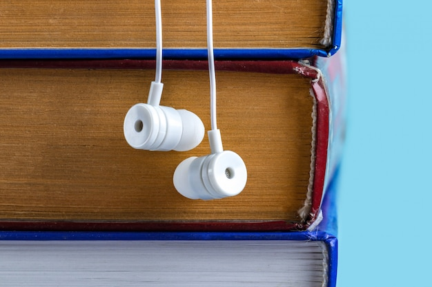 Hörbuch-konzept. weiße kopfhörer und bücher. bücher lesen, ohne von der arbeit aufzublicken Premium Fotos