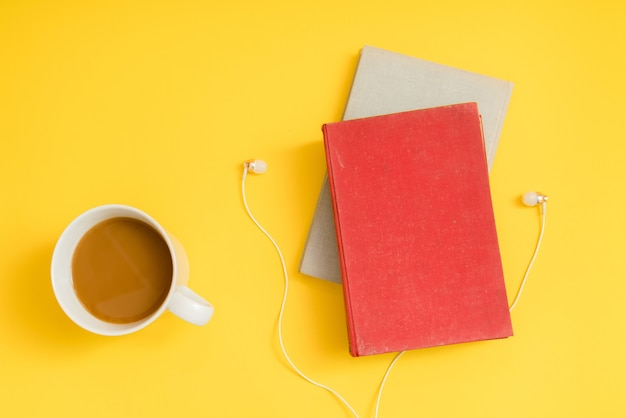 Hörbuchkonzept. kopfhörer, kaffee und hardcover-buch über gelbem tisch. Premium Fotos