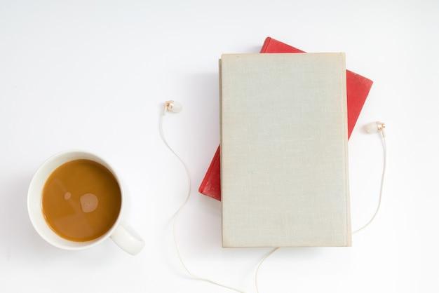 Hörbuchkonzept. kopfhörer, kaffee und hardcover über dem tisch. Premium Fotos