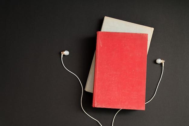 Hörbuchkonzept. kopfhörer und buch über schwarzem tisch. Premium Fotos