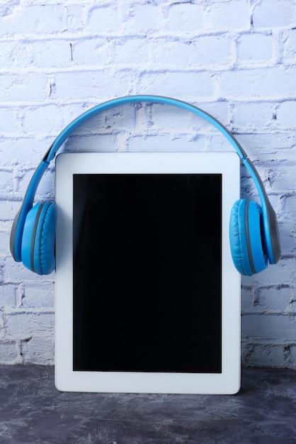 Hörbuchkonzept. kopfhörer und digitales tablet auf dem tisch. Premium Fotos
