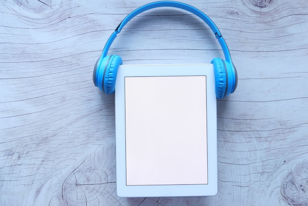 Hörbuchkonzept. kopfhörer und digitales tablet auf dem tisch Premium Fotos