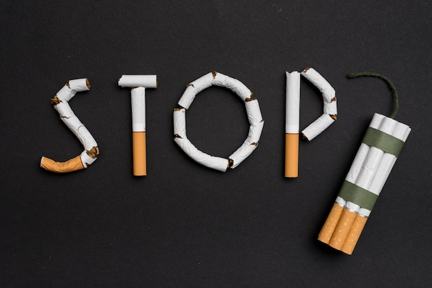 Hören sie auf, konzept mit bündel zigaretten und docht gegen schwarzen hintergrund zu rauchen Kostenlose Fotos