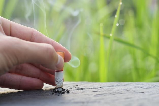 Hören sie auf zu rauchen, hören sie auf zu rauchen konzept, hand fallengelassene zigarette kam unten zum holztisch, um zu rauchen aufzuhören. Premium Fotos
