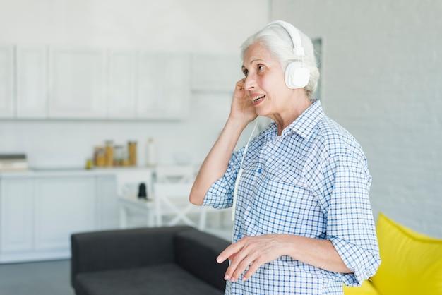 Hörende musik der älteren frau auf kopfhörer zu hause Kostenlose Fotos
