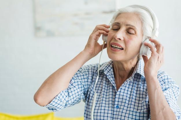 Hörende musik der älteren frau auf kopfhörer Kostenlose Fotos