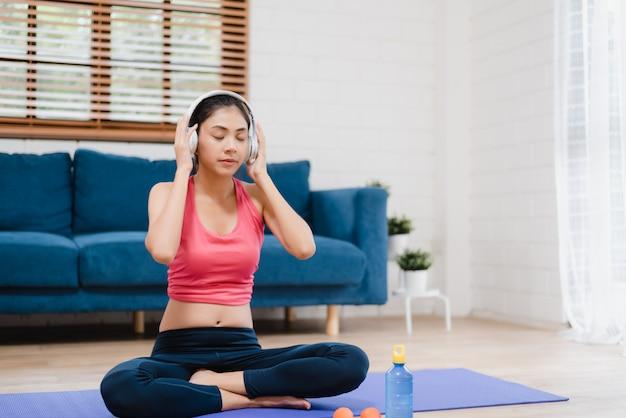 Hörende musik der jungen asiatin beim üben von yoga im wohnzimmer Kostenlose Fotos