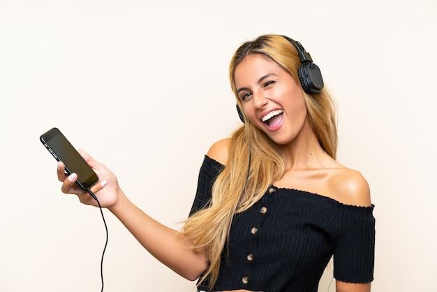 Hörende musik der jungen blondine mit einem mobile und gesang über lokalisierter wand Premium Fotos
