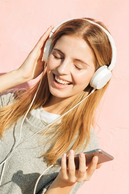 Hörende musik der jungen frau auf kopfhörer befestigen durch handy gegen rosa hintergrund Kostenlose Fotos