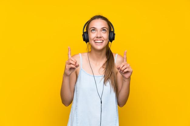 Hörende musik der jungen frau über lokalisierter gelber wand eine großartige idee oben zeigend Premium Fotos