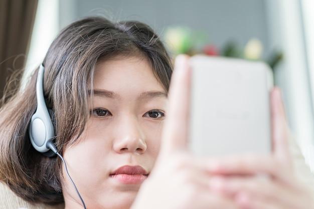 Hörende musik der jungen frau vom handy Premium Fotos