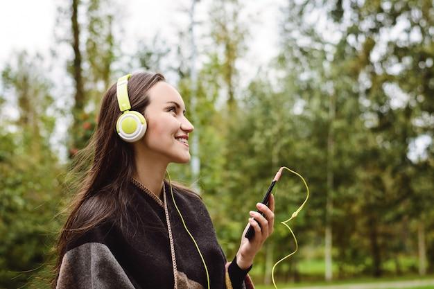 Hörende musik der jungen glücklichen frau vom smartphone mit kopfhörern in einem ruhigen park Premium Fotos