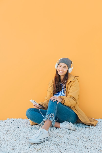 Hörende musik der netten frau am intelligenten telefon, das auf wolldecke gegen gelbe oberfläche sitzt Kostenlose Fotos