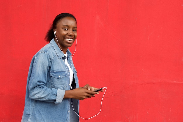 Hörende musik der schönen afrikanischen frau auf mobile Premium Fotos