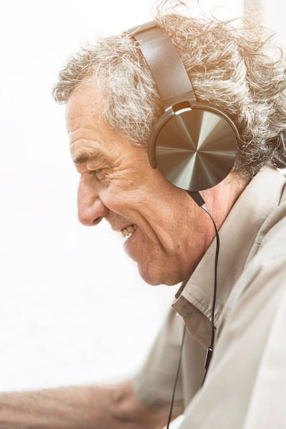 Hörende musik des älteren mannes auf kopfhörer gegen weißen hintergrund Kostenlose Fotos