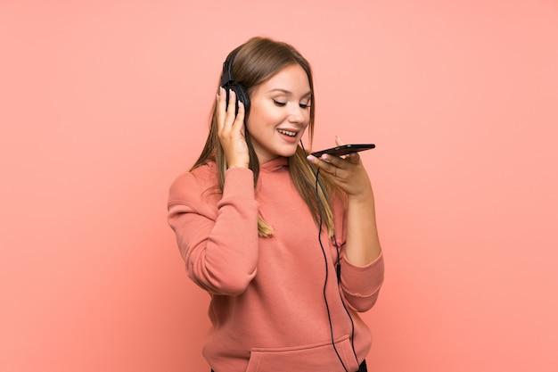 Hörende musik des jugendlichmädchens mit einem mobile über lokalisiertem rosa hintergrund Premium Fotos