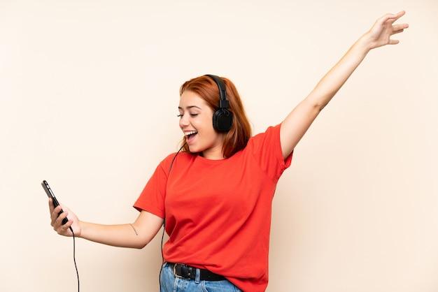 Hörende musik des jugendlichrothaarigemädchens mit einem mobile über lokalisierter wand Premium Fotos