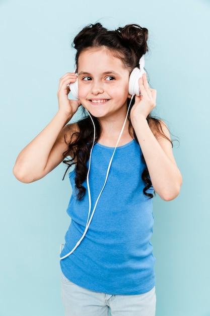 Hörende musik des jungen mädchens der vorderansicht Kostenlose Fotos