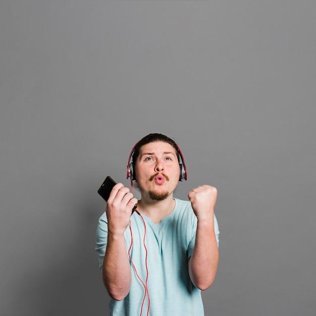 Hörende musik des jungen mannes auf dem kopfhörer, der gegen graue wand schmollt Kostenlose Fotos