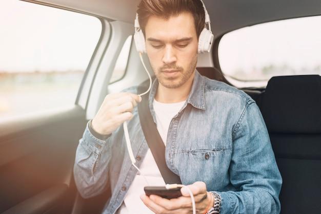 Hörende musik des jungen mannes auf kopfhörer beim reisen in das auto Kostenlose Fotos